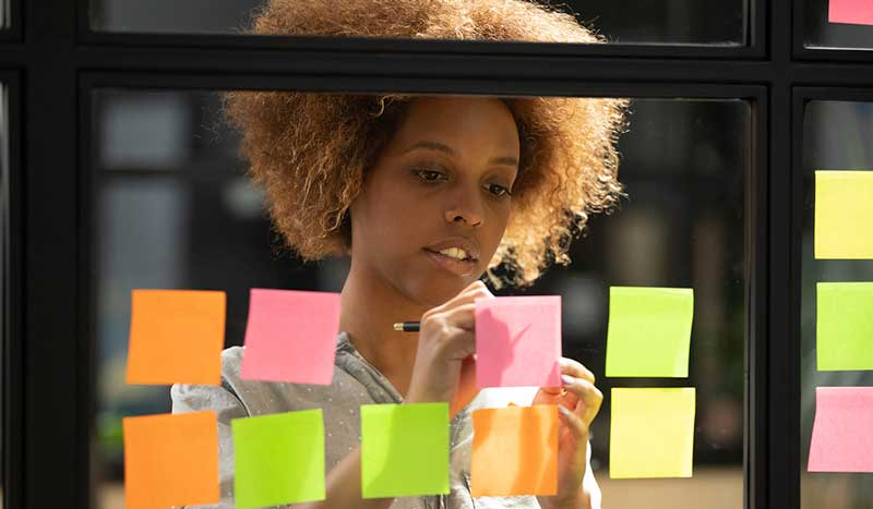 African-woman-writing-down-on-sticky-notes-view-through-glass